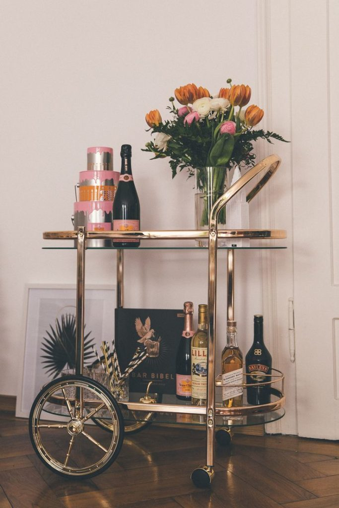 Bar Cart Styling - golding service car in retro look with bunch of flowers