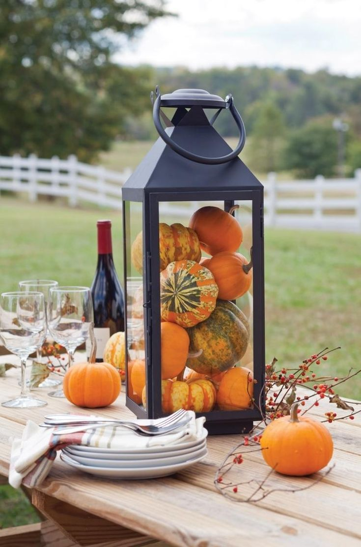 Legend Small decorative pumpkins as a table decoration in huge candle lantern ...